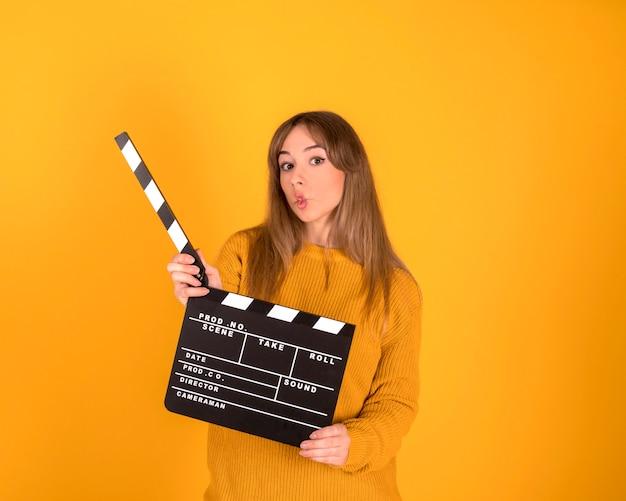 Retrato de uma mulher bonita e feliz com a boca fechada, com claquete de cinema, em fundo amarelo-laranja
