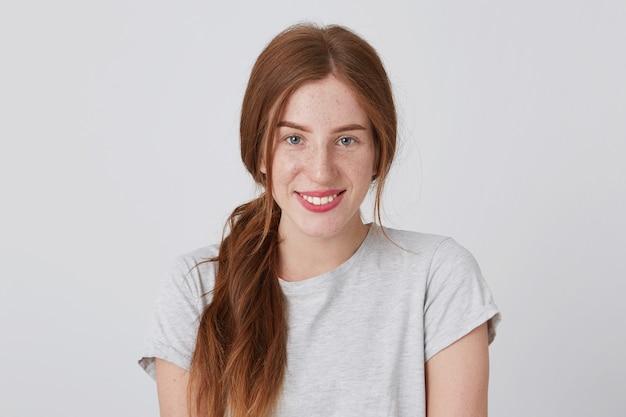 Retrato de uma mulher bonita e feliz, com longos cabelos ruivos e sardas, sorri e olha diretamente para a frente
