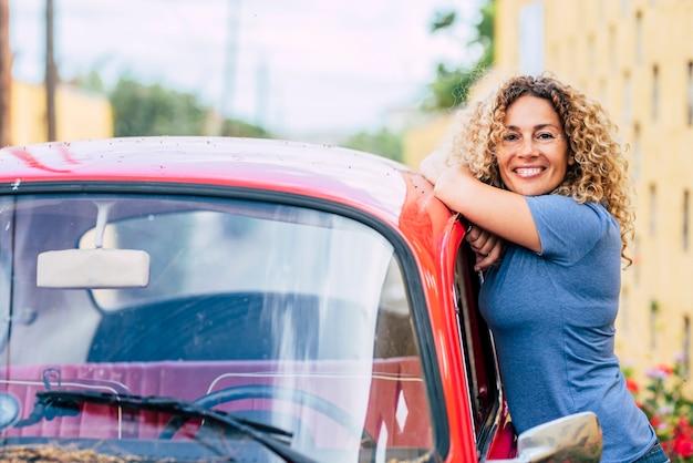 Retrato de uma mulher bonita e feliz de meia-idade, do lado de fora de seu carro vermelho clássico, sorrindo