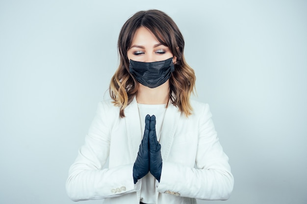Retrato de uma mulher bonita e jovem médica em um vestido branco de médico, luvas de borracha pretas e máscara preta no rosto, medita e pratica ioga em um fundo branco