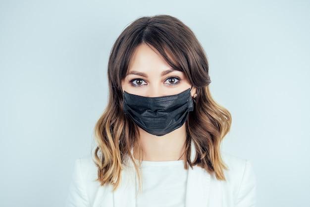 Retrato de uma mulher bonita e jovem médica em um vestido branco médico e máscara preta no rosto em um fundo branco