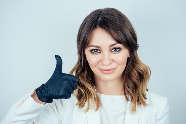 Retrato de uma mulher bonita e jovem médica em um vestido branco médico, luvas de borracha pretas polegares para cima em um fundo branco