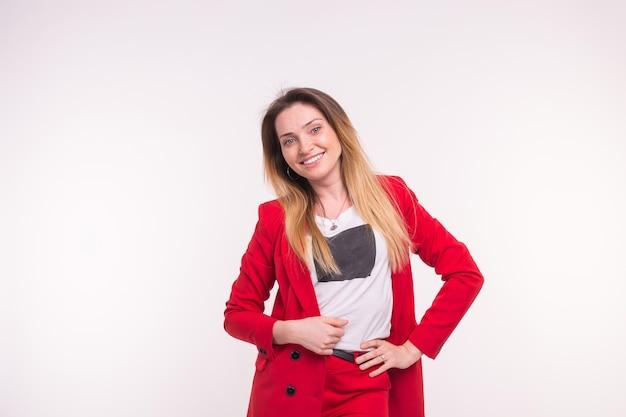 Retrato de uma mulher bonita e sardenta sorridente, vestindo um terno vermelho sobre fundo branco com espaço de cópia