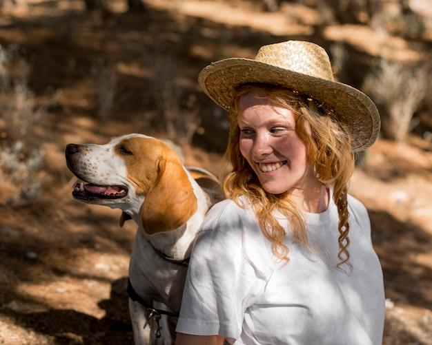 Retrato de uma mulher bonita e seu cachorro olhando para longe