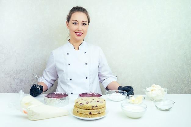 Retrato de uma mulher bonita e sorridente confeiteiro em luvas pretas e uniforme de trabalho branco com um delicioso bolo acabado de fazer na mesa. confeiteiro, bolo, culinária.
