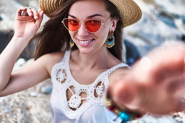 Retrato de uma mulher bonita e sorridente verão elegante com um chapéu de palha e óculos de sol vermelhos, vestindo uma blusa branca