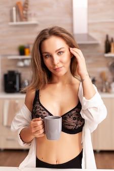 Retrato de uma mulher bonita em lingerie sexy segurando uma xícara de café durante o café da manhã na cozinha de casa. jovem mulher atraente com tatuagens em roupa interior sedutora.