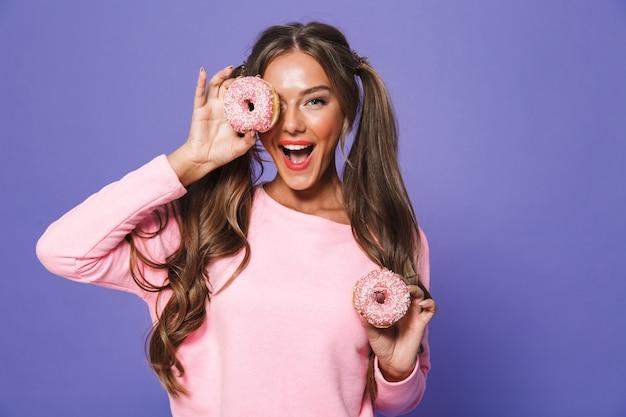 Retrato de uma mulher bonita em moletom posando com donuts