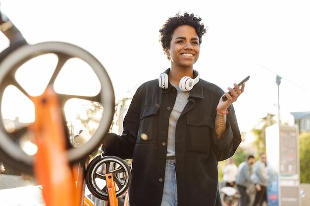 Retrato de uma mulher bonita em pé com fones de ouvido e celular perto de estacionamento para scooters no parque da cidade