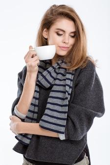 Retrato de uma mulher bonita em pé com uma xícara de café isolada em um fundo branco