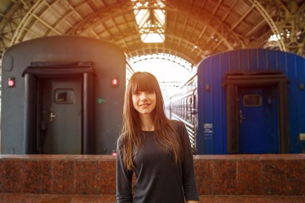 Retrato de uma mulher bonita em pé na estação ferroviária, perto do trem