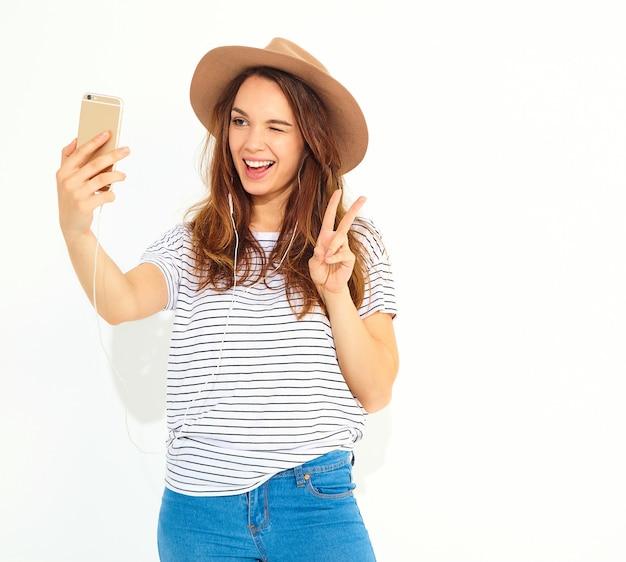 Retrato de uma mulher bonita em roupas de hipster de verão tomando uma selfie isolada na parede branca. piscando e mostrando sinal de paz