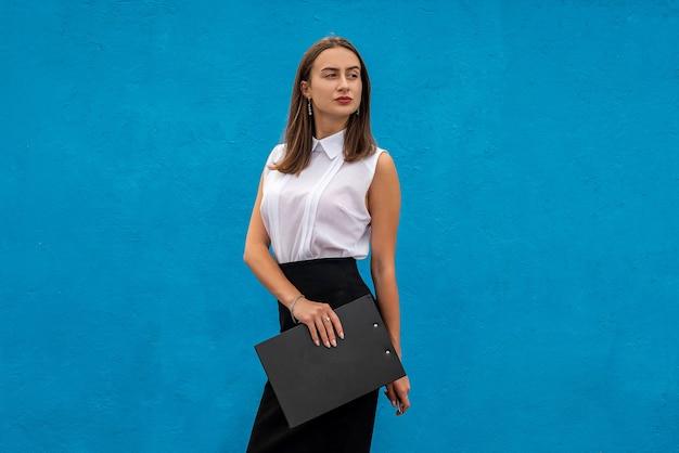 Retrato de uma mulher bonita em roupas de negócios com a escrita da prancheta, isolada em azul