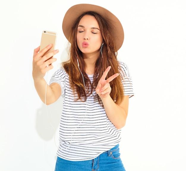 Retrato de uma mulher bonita em roupas de verão hipster tomando uma selfie isolada na parede branca