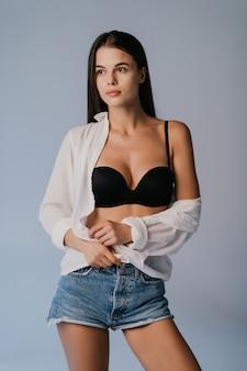 Retrato de uma mulher bonita em shorts jeans e lingerie isolado na cinza