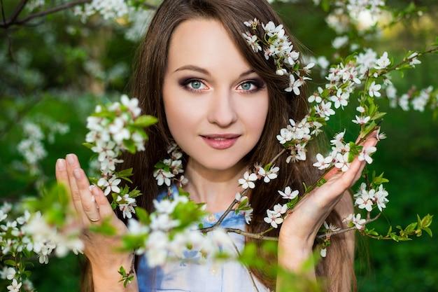 Retrato de uma mulher bonita em um jardim de cerejeira em flor