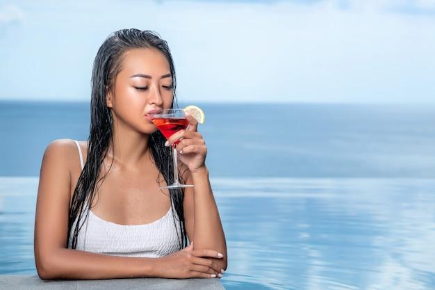 Retrato de uma mulher bonita em um top branco que bebe de cocktail cosmopolita. vista para o mar em fundo desfocado. piscina infinita nos fundos desfocados
