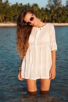 Retrato de uma mulher bonita em um vestido branco andando na água em uma praia tropical ao pôr do sol usando óculos de sol elegantes