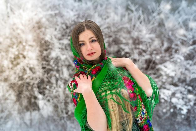 Retrato de uma mulher bonita em um xale verde na floresta de inverno