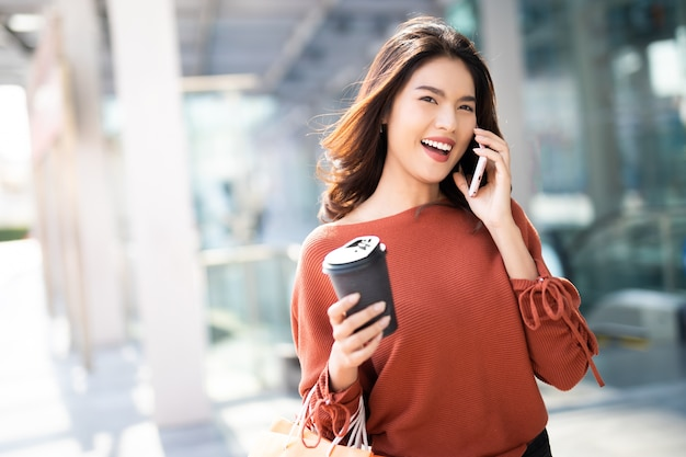 Retrato de uma mulher bonita feliz segurando a xícara de café enquanto estiver usando smartphone