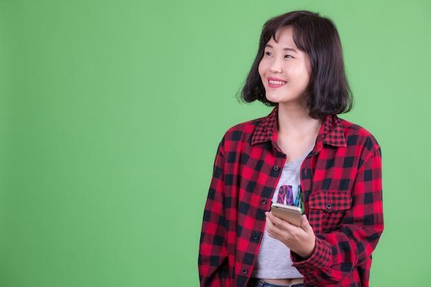 Retrato de uma mulher bonita hippie asiática com cabelo curto contra chroma key ou parede verde