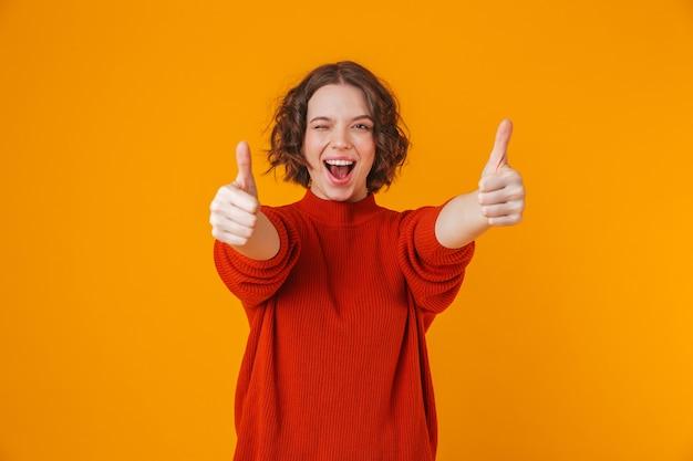 Retrato de uma mulher bonita jovem feliz posando isolado sobre a parede amarela aparecendo os polegares.