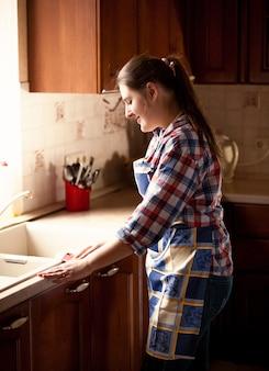 Retrato de uma mulher bonita limpando a cozinha com um pano