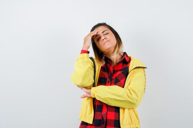 Retrato de uma mulher bonita mantendo a mão na cabeça em uma camisa, jaqueta e parecendo uma vista frontal cansada