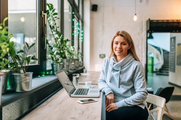 Retrato de uma mulher bonita na roupa ocasional que senta-se no café na frente do portátil. olhando para a câmera.