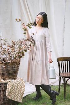 Retrato de uma mulher bonita no jardim, em pé e segurando a planta durante o dia.
