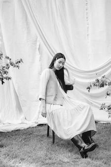 Retrato de uma mulher bonita no jardim, sentado em uma cadeira e olhando no vestido cor creme durante o dia. preto e branco