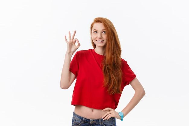 Retrato de uma mulher bonita no vestido vermelho de papai noel mostrando sinal okey e piscando sobre branco