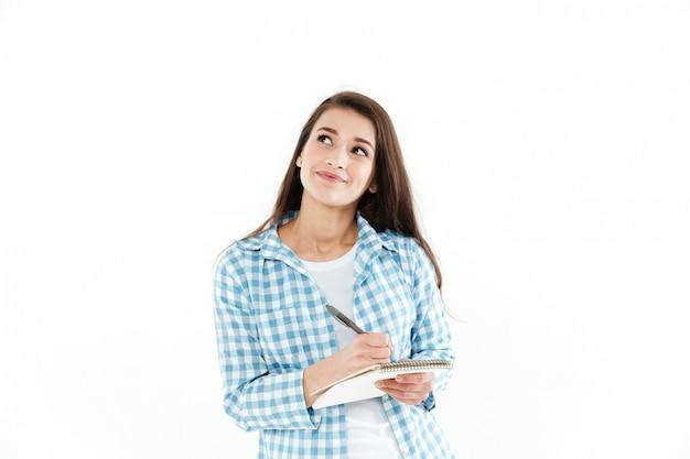 Retrato de uma mulher bonita pensativa, fazendo anotações