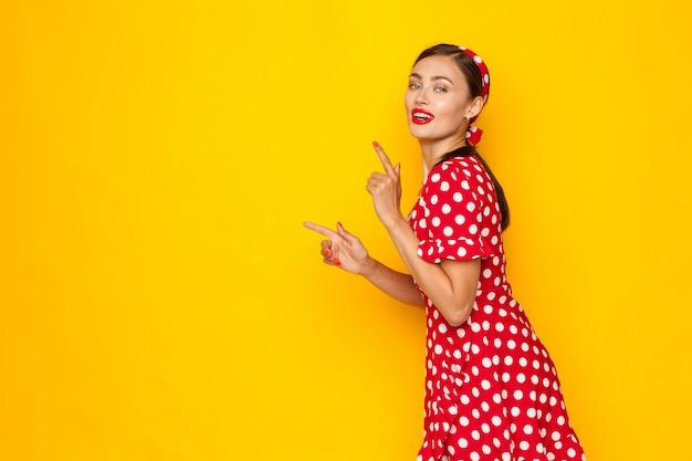 Retrato de uma mulher bonita pin-up estilo retro apontando