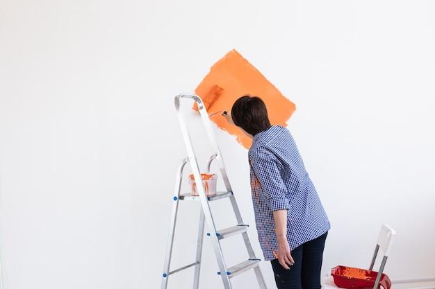Retrato de uma mulher bonita pintando uma parede em um apartamento novo