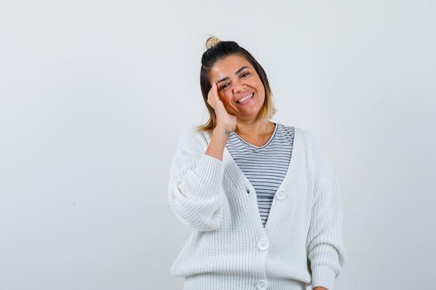 Retrato de uma mulher bonita posando com a mão na lateral do rosto em uma camiseta, casaco de lã e parecendo jovial