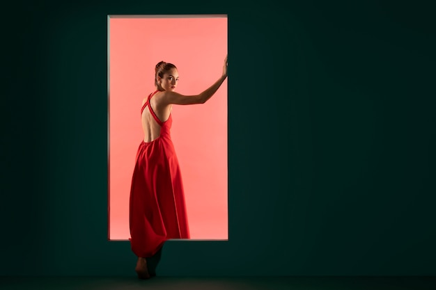 Retrato de uma mulher bonita posando com um vestido vermelho esvoaçante