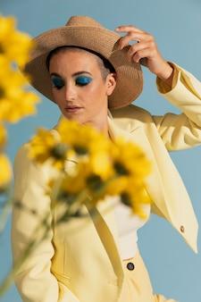 Retrato de uma mulher bonita posando com uma jaqueta amarela e flores
