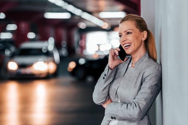 Retrato de uma mulher bonita que ri ao falar no telefone esperto no estacionamento subterrâneo, espaço da cópia.