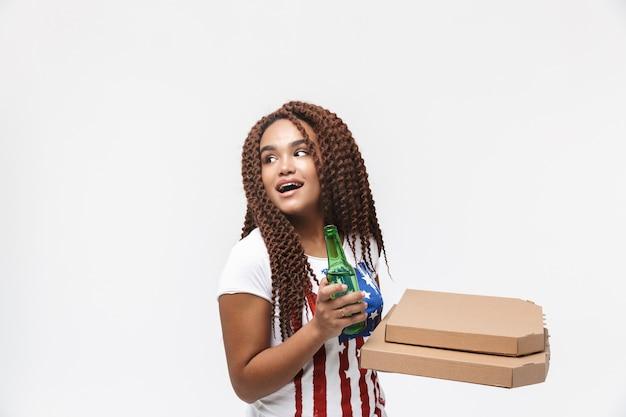 Retrato de uma mulher bonita segurando caixas de pizza e uma garrafa de cerveja durante o jogo de futebol isolado contra uma parede branca