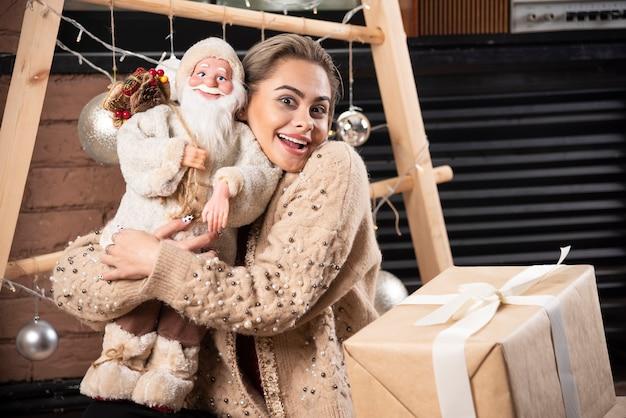Retrato de uma mulher bonita sentada e segurando um brinquedo de papai noel. foto de alta qualidade