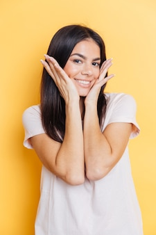 Retrato de uma mulher bonita sorridente, olhando para a frente sobre uma parede amarela