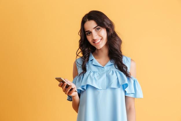 Retrato de uma mulher bonita sorridente segurando um smartphone e isolado