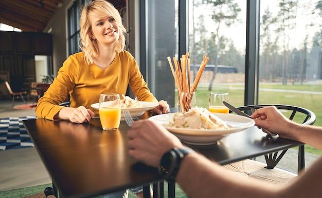 Retrato de uma mulher bonita sorridente, sentada à mesa com um jovem homem branco