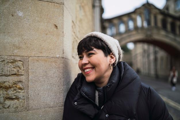 Retrato de uma mulher branca e sorridente atraente, com um chapéu e um casaco encostado na parede