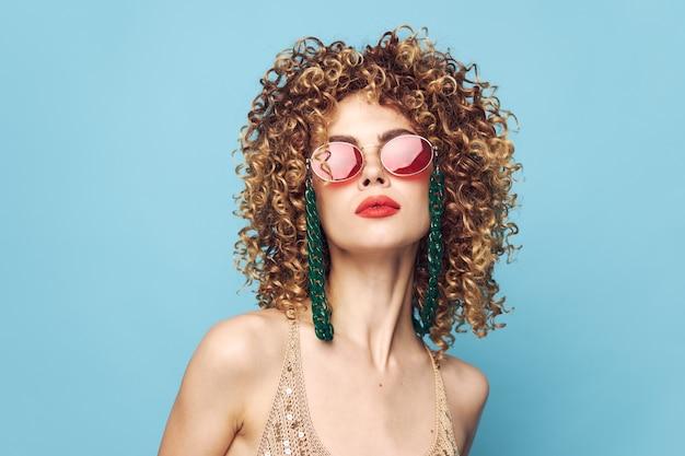 Retrato de uma mulher cabelo encaracolado joalheria óculos maquiagem brilhante