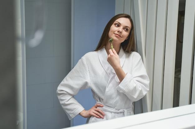 Retrato de uma mulher caucasiana atraente e satisfeita se olhando no espelho do banheiro