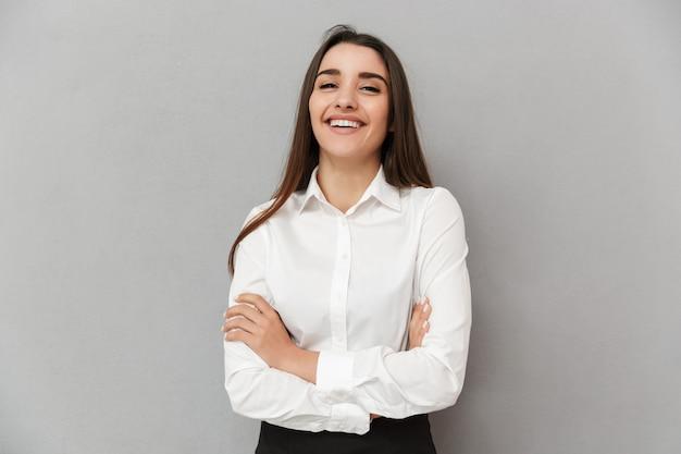 Retrato de uma mulher caucasiana com belos cabelos castanhos compridos em roupa de trabalho sorrindo e mantendo os braços cruzados, isolado sobre uma parede cinza
