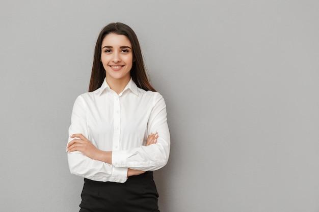 Retrato de uma mulher caucasiana com cabelos castanhos compridos em roupa de trabalho sorrindo e mantendo os braços cruzados, isolado sobre uma parede cinza