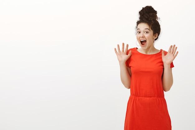 Retrato de uma mulher caucasiana de cabelos cacheados feliz e animada com um corte de cabelo em forma de coque, sorrindo amplamente e gritando de espanto e surpresa